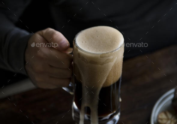 Overflowing pint of beer - Stock Photo - Images