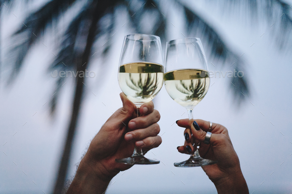 Couple enjoying a glass of wine by the beach - Stock Photo - Images