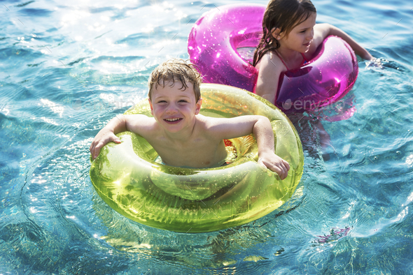 Cheerful brother and sister swimming in the pool - Stock Photo - Images