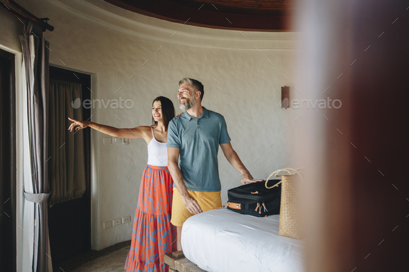 Honeymooners checking in to a hotel room - Stock Photo - Images