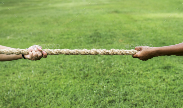 Closeup of hand pulling the rope in tug of war game - Stock Photo - Images