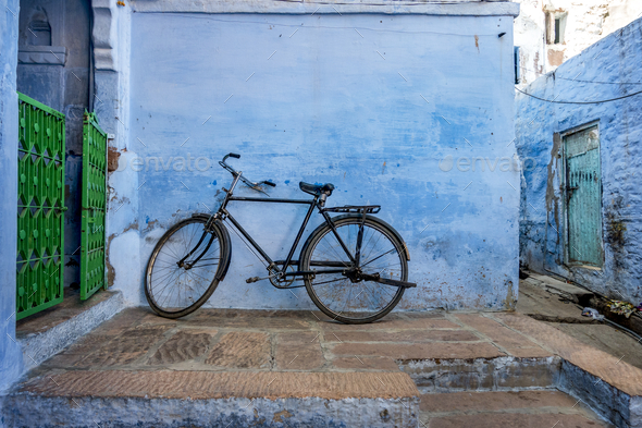 Bicycle leaning on the blue wall - Stock Photo - Images