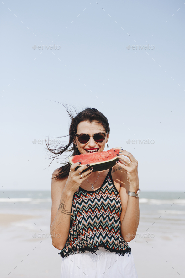 Woman eating watermelon at the beach - Stock Photo - Images