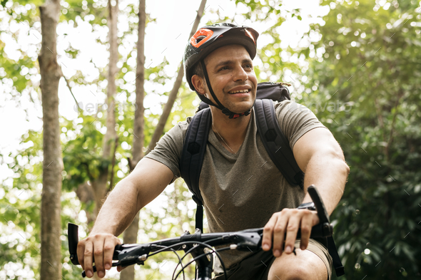 Happy cyclist riding through the forest - Stock Photo - Images