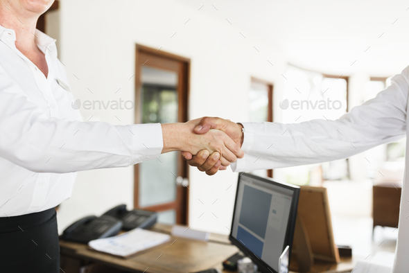 Receptionist is greeting hotel guest - Stock Photo - Images