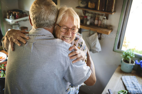 Senior couple hugging in the kitchen - Stock Photo - Images