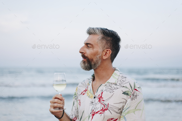 Man drinking a glass of wine by the beach - Stock Photo - Images