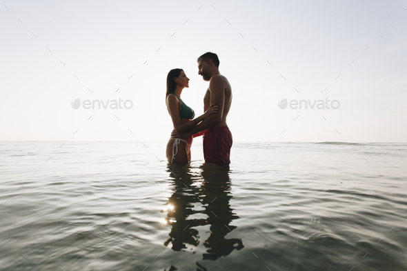 Romantic couple in the sea at sunset - Stock Photo - Images