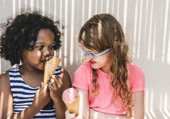 Little girls enjoying with ice cream - Stock Photo - Images