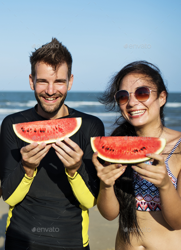 Couple eating watermelon on summer beach - Stock Photo - Images
