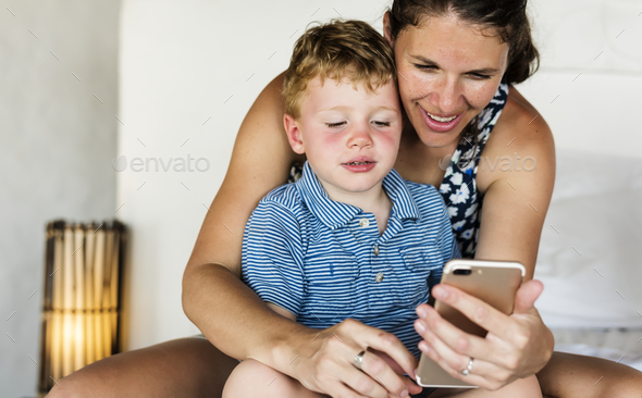 Mother sitting with son on bed using mobile - Stock Photo - Images