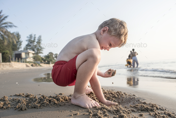 A little boy playing in the sand - Stock Photo - Images