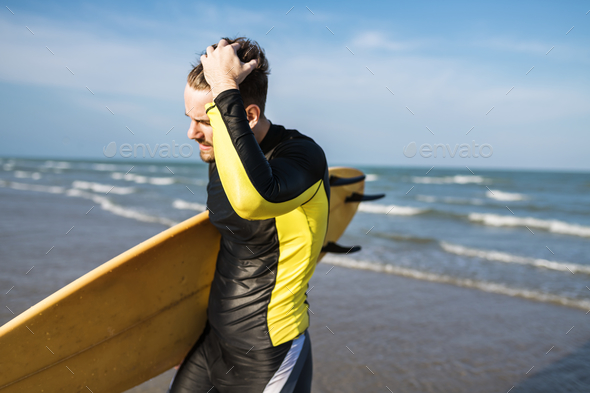 A man carrying a surfboard - Stock Photo - Images