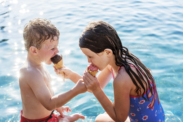 Child sharing an ice cream by the pool - Stock Photo - Images