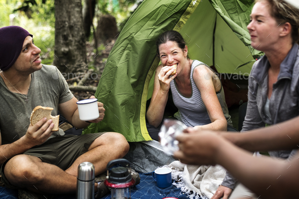 Group of diverse friends camping in the forest - Stock Photo - Images