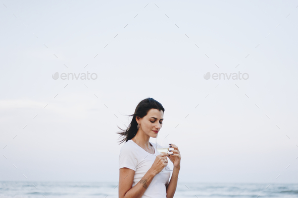 Woman drinking a glass of wine by the beach - Stock Photo - Images