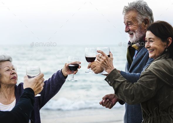 Mature friends drinking wine at the beach - Stock Photo - Images