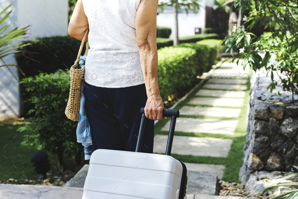 Senior woman pulling suitcase and walking - Stock Photo - Images
