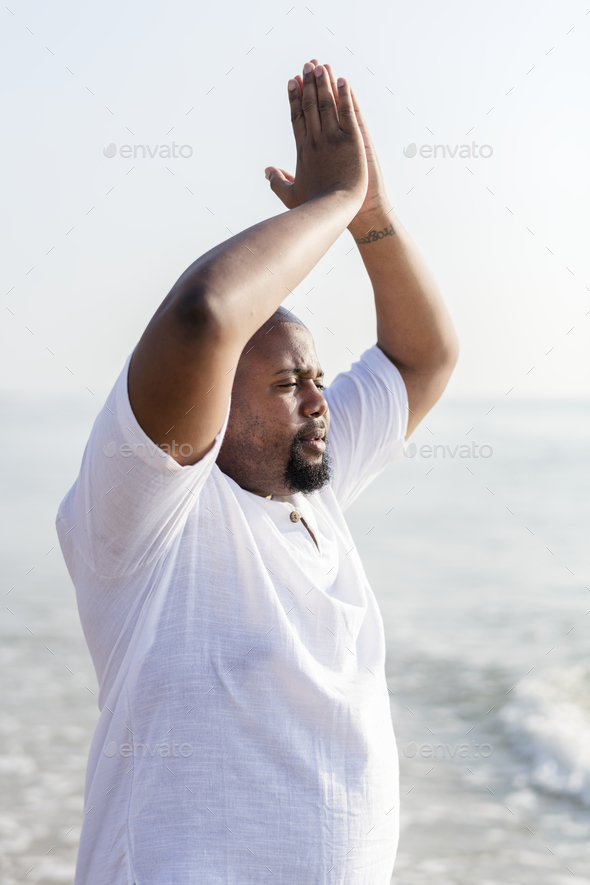 African American man practicing yoga at the beach - Stock Photo - Images
