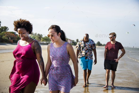 Group of friends walking on the beach - Stock Photo - Images
