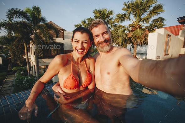 Couple taking a selfie in a pool - Stock Photo - Images