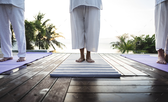 Group of seniors practicing yoga by the pool - Stock Photo - Images