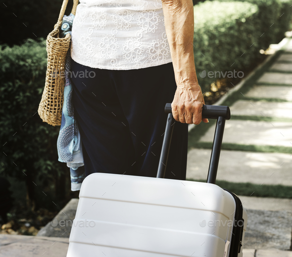 Senior woman pulling a suitcase - Stock Photo - Images