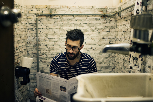 Man in a restroom reading newspaper - Stock Photo - Images