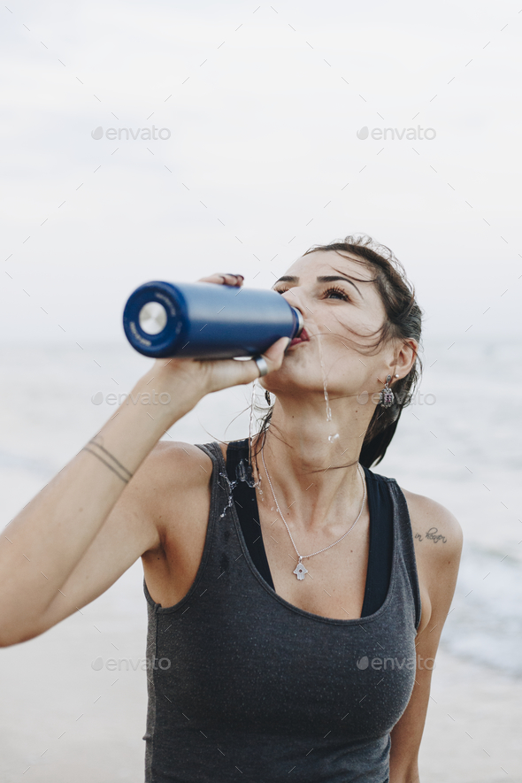 Woman drinking water after a workout - Stock Photo - Images