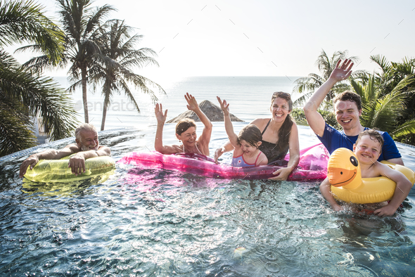 Family playing in a pool - Stock Photo - Images