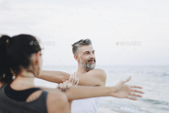 Couple stretching at the beach - Stock Photo - Images