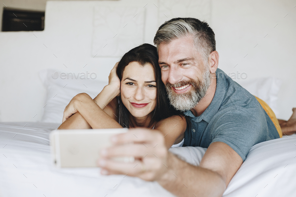 Honeymooners taking a selfie in bed - Stock Photo - Images