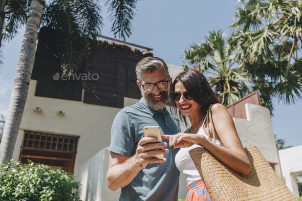 Couple using their phone while on vacation - Stock Photo - Images