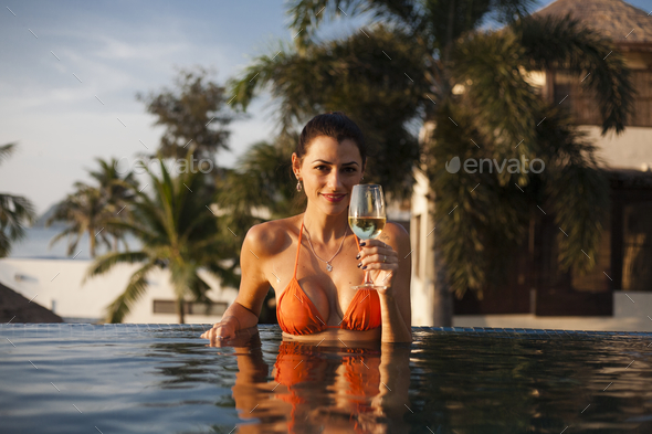 Beautiful woman relaxing in a swimming pool - Stock Photo - Images