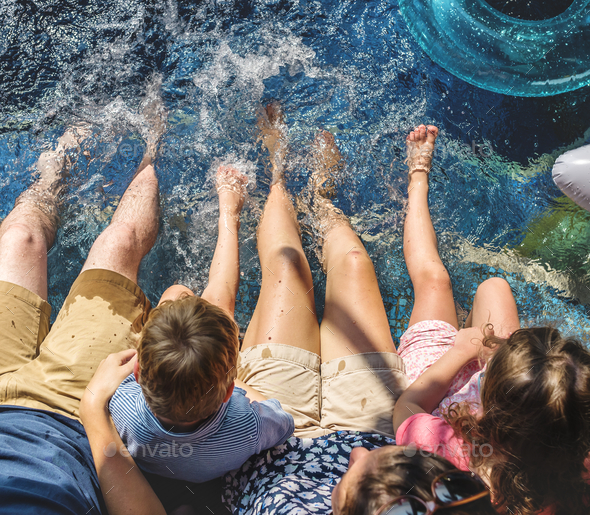 Family sitting by the pool - Stock Photo - Images