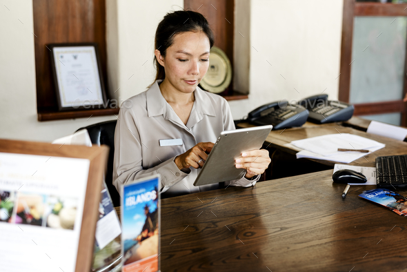 Receptionist working at the front desk - Stock Photo - Images