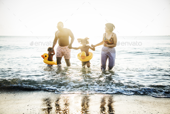 Family playing together at the beach - Stock Photo - Images