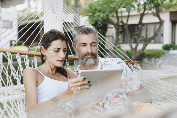 Couple using a tablet in a hammock - Stock Photo - Images