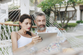Couple using a tablet in a hammock - PhotoDune Item for Sale