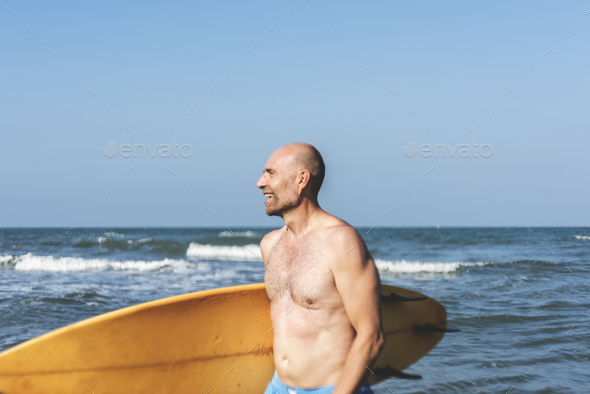 A man with a surfboard by the coast - Stock Photo - Images