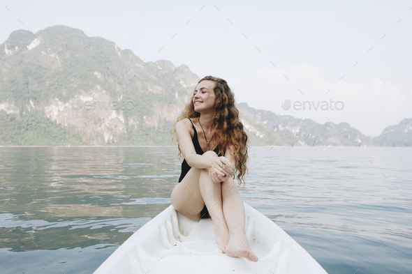 Woman relaxing on a canoe at a lake - Stock Photo - Images