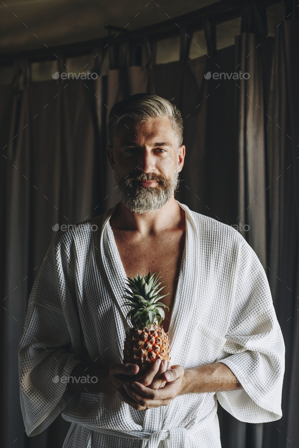Man in a bathrobe holding a pineapple - Stock Photo - Images