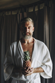 Man in a bathrobe holding a pineapple - PhotoDune Item for Sale