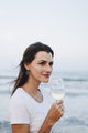 Woman drinking a glass of wine by the beach - PhotoDune Item for Sale