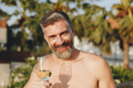 Handsome man having a glass of wine in the pool - PhotoDune Item for Sale