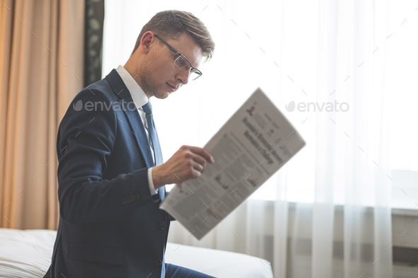 Young businessman in a suit reading a newspaper - Stock Photo - Images