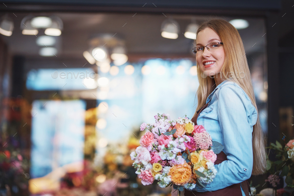 Smiling woman with a bouquet of flowers - Stock Photo - Images