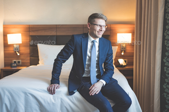 Smiling businessman in a suit in bedroom - Stock Photo - Images