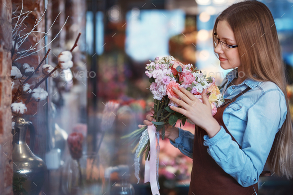Young florist with a bouquet of flowers - Stock Photo - Images