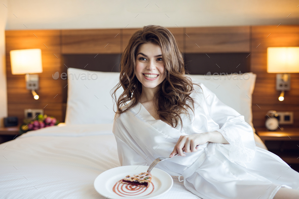 Young woman eating breakfast - Stock Photo - Images